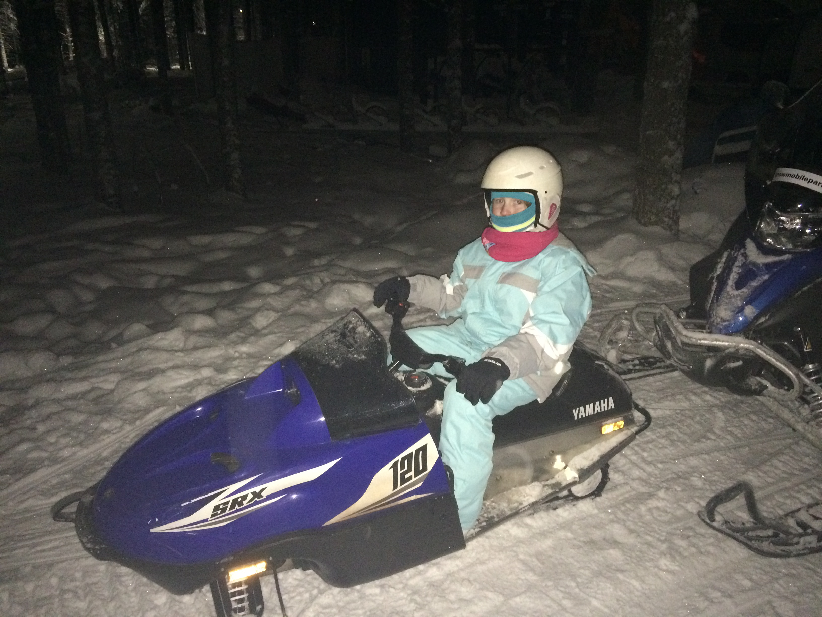 Lily-Belle sits astride a snowmobile in Rovaniemi, Lapland