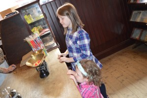 Lily-Belle and Matilda peer over the counter at W.G. O'Doherty sweet shop at the Ulster American Folk Park and Museum