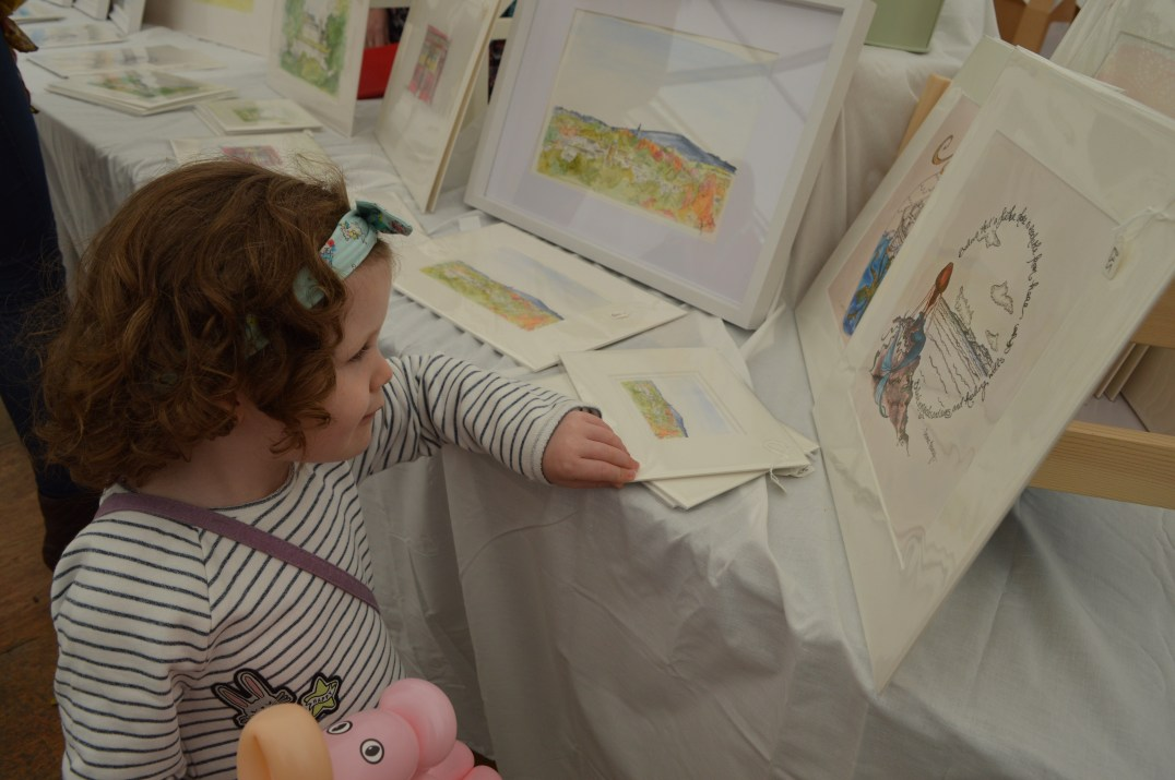 Matilda looking at illustrations by Inspired by Astrid