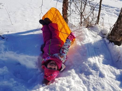 Matilda sledding at A Cosy Cottage by the River, Rovaniemi