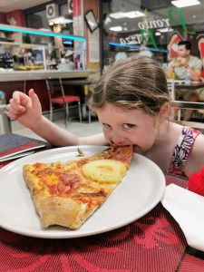 Matilda tackling a slice of pizza at Pronto Pizza in Predazzo