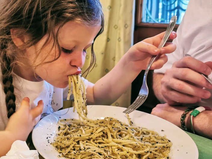 Matilda eating pesto spaghetti at Franco's in Cavalese