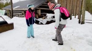 Cleaning reindeer poop off our shoes at Vaara Reindeer Farm Ranua