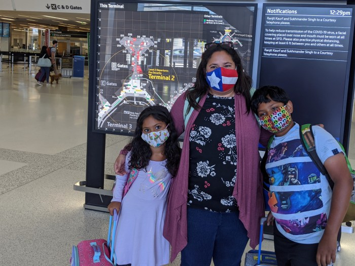 Mom and two kids wearing masks at the airport