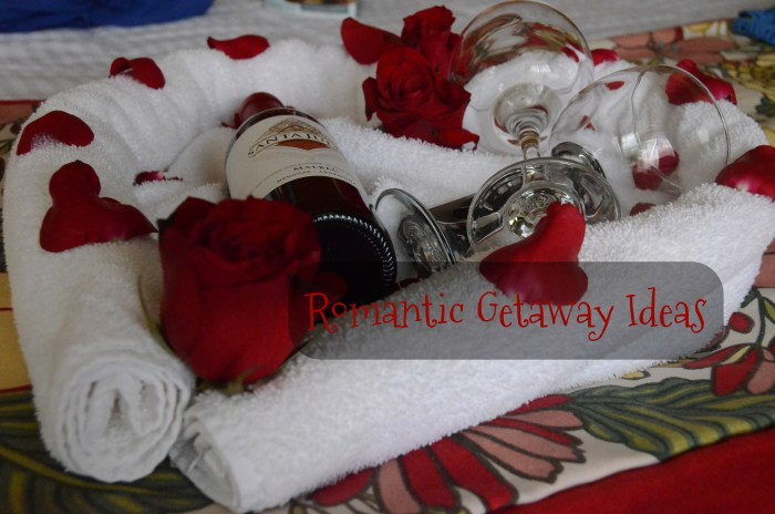 Two glasses with a bottle of wine, with rose petals in a towel heart