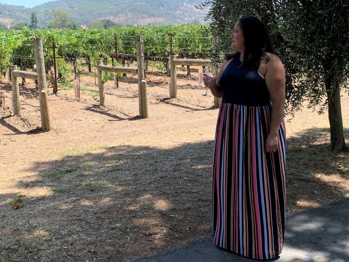 Woman drinking wine in front of a vineyard