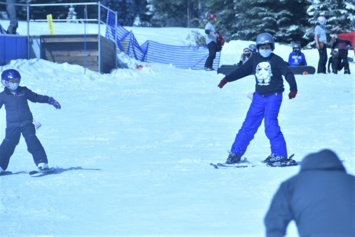 A young man skiing with a black sweatshirt and blue snow pants.  He is skiing next to a young girl in purples ski gear.