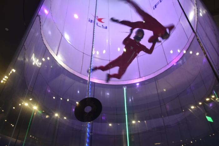 A young girl and the instructor flying up high in the indoor skydiving tube