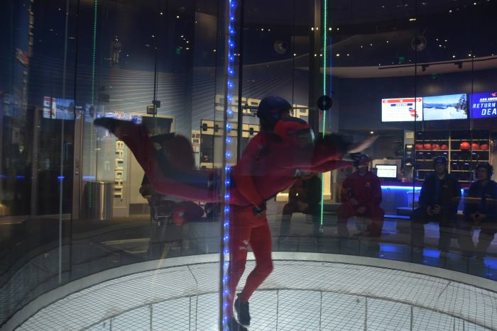 Instructor helping a young man in the indoor skydiving tube