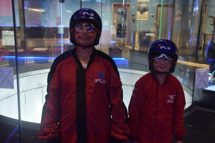 Two children in flight suits, helmets and goggles