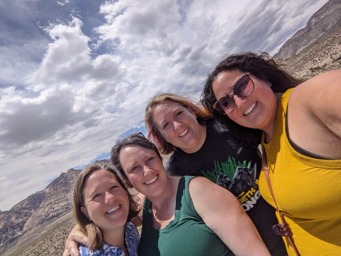 4 women in front of hills, dessert and dramatic sky