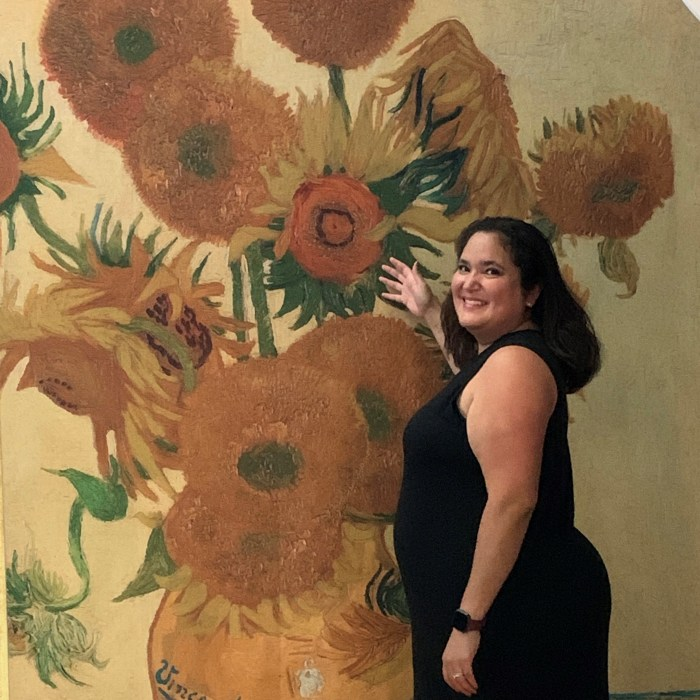 A woman in a black dress in front of the Van Gogh sunflowers painting