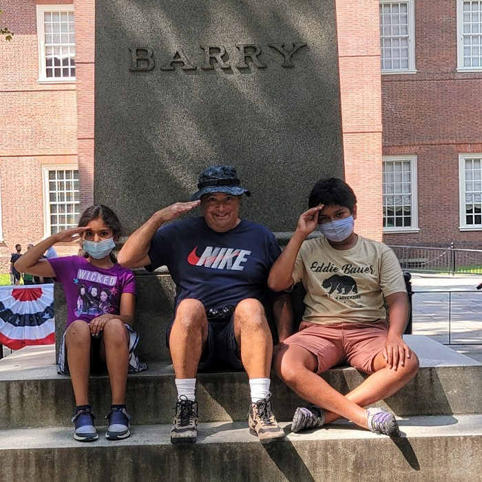 3 people saluting in front of the John Barry Statue in Philadelphia