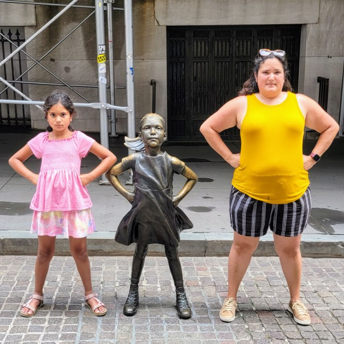 A woman and young girl along side the Fearless Girl Sculpture
