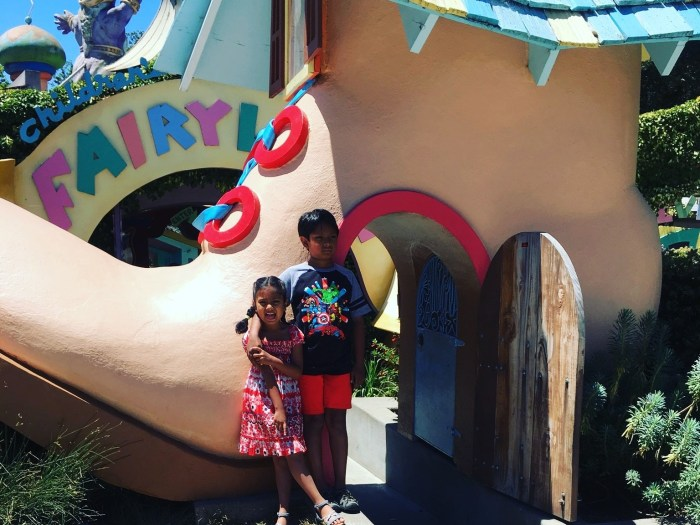 A young girl and boy in front of the shoe-house in front of Children's Fairyland