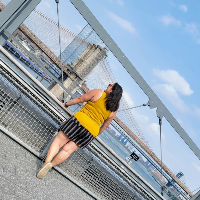 A woman standing on top of Pier 17 looking at the Brooklyn Bridge