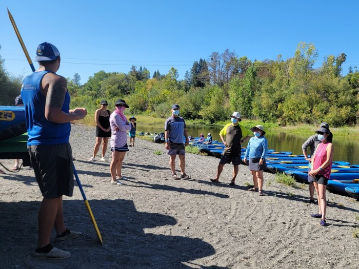 People listening to an instructor in front of blue inflatable kayaks on the Russian River