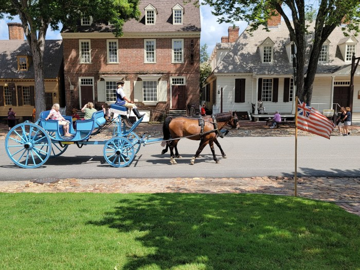 A blue horse drawn carriage with a family being pulled down the street in Colonial Williamsburg