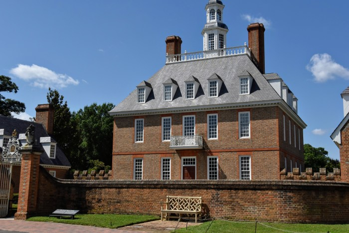 3 story 18th century brick mansion with a brick wall around the front yard