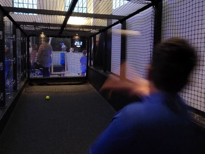 A young man throwing a ball in a batting cage at 26.3 MPH