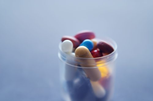 Pot of different coloured pills closeup with a negative space background.