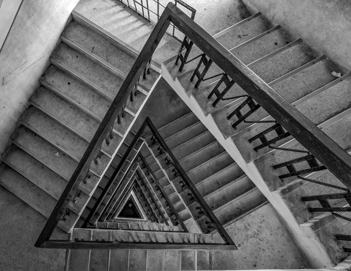 Triangular spiral staircase in black and white.
