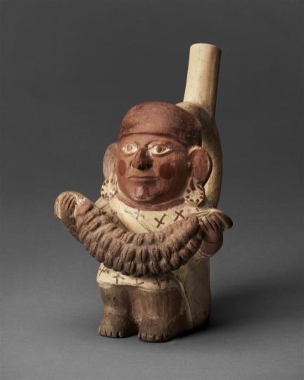 Personaje con semillas Botella de asa estribo de estilo mochica (200-850 d.C.) con representación de personaje que sostiene un grupo de semillas de nectandra. Foto: Museo Nacional de Arqueología, Antropología e Historia del Perú, Ministerio de Cultura del Perú / MALI