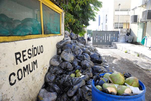 Lixo vem sendo depositado já fora da lixeira, no chão, junto à cozinha do hospital. O acúmulo já dura mais de uma semana
