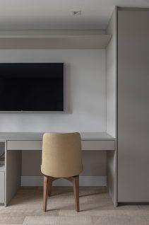 Para o espaço de home office abaixo de TV, a marcenaria cinza com a cadeira caramelo promovem sintonia com o restante do ambiente.