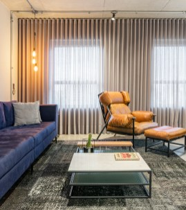 No living, destaque para o sofá no tom azul marinho e na poltrona de couro.