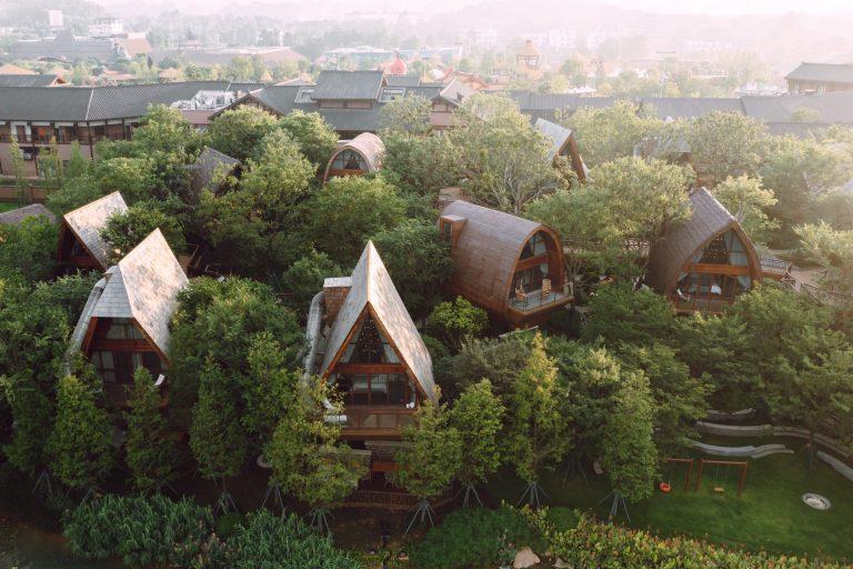 Imagem do hotel construído entre as árvores.