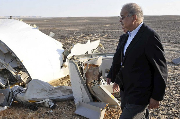 Egypt's Prime Minister Sherif Ismail looks at the remains of a plane crash at the desert in central Sinai near El Arish city
