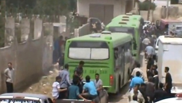 "An image grab taken from a video released by Syria Mubasher Network on May 7, 2014 allegedly shows the evacuation of a besieged opposition-held area in Syria's central city of Homs after a deal between the Syrian regime and the rebels was reached. The deal was reached as part of an exchange for a number of hostages being held by opposition fighters in the northern city of Aleppo. Once the Homs operation is complete, the evacuated areas are to be turned over to the government, which is expected to send in forces to sweep for mines and explosives. AFP PHOTO / DSK / SYRIA MUBASHER NETWORK === RESTRICTED TO EDITORIAL USE - MANDATORY CREDIT ""AFP PHOTO/DSK/SYRIA MUBASHER NETWORK"" - NO MARKETING NO ADVERTISING CAMPAIGNS - DISTRIBUTED AS A SERVICE TO CLIENTS FROM ALTERNATIVE SOURCES, THEREFORE AFP IS NOT RESPONSIBLE FOR ANY DIGITAL ALTERATION==="