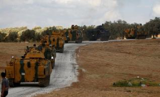 A Turkish military convoy drives by a village on the Turkish-Syrian border line in Reyhanli