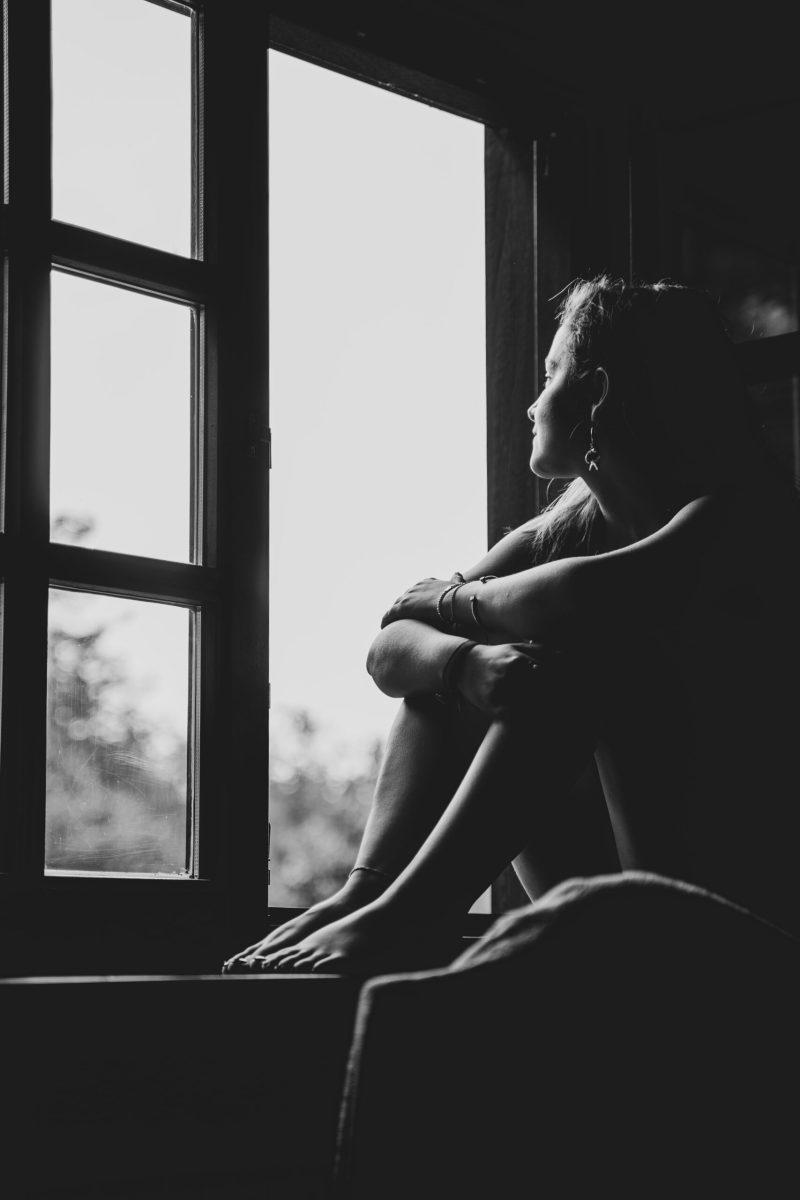 Frau schaut aus dem Fenster und philosophiert