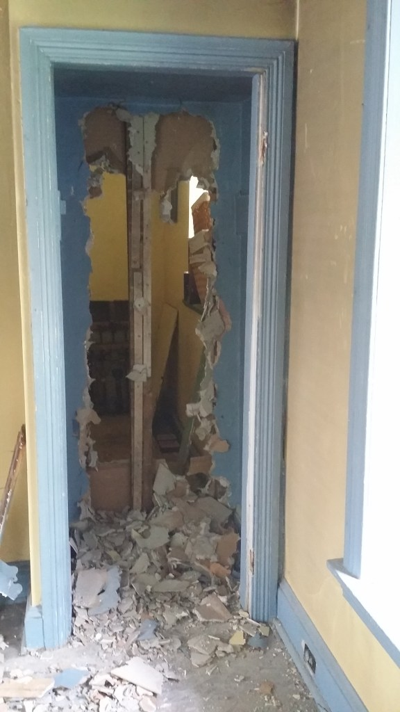 The back wall of the small bedroom closet is torn out to create the entrance to the new walk-in closet.