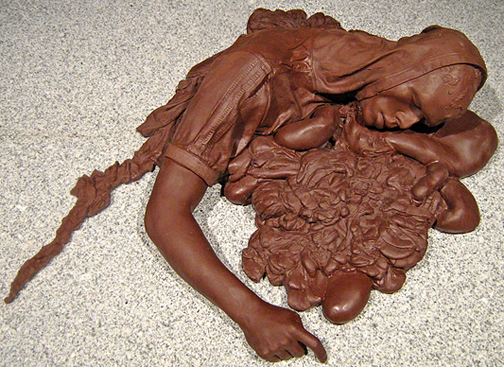 """""""On the road to Heaven the Highway to Hell."""" Sculpture cast in dark chocolate depicting remains of a suicide bomber."""