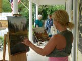 Artist Shar Brecht paints on the porch of The Creator's Gallery