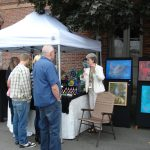 Jannie entertains visitors to her booth as companion artist Alx Fox looks on