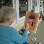 Ruth Heath paints on the porch of The Creator's Gallery