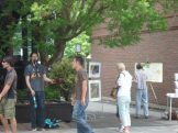 Anne Brooke paints despite the distraction of a juggler nearby
