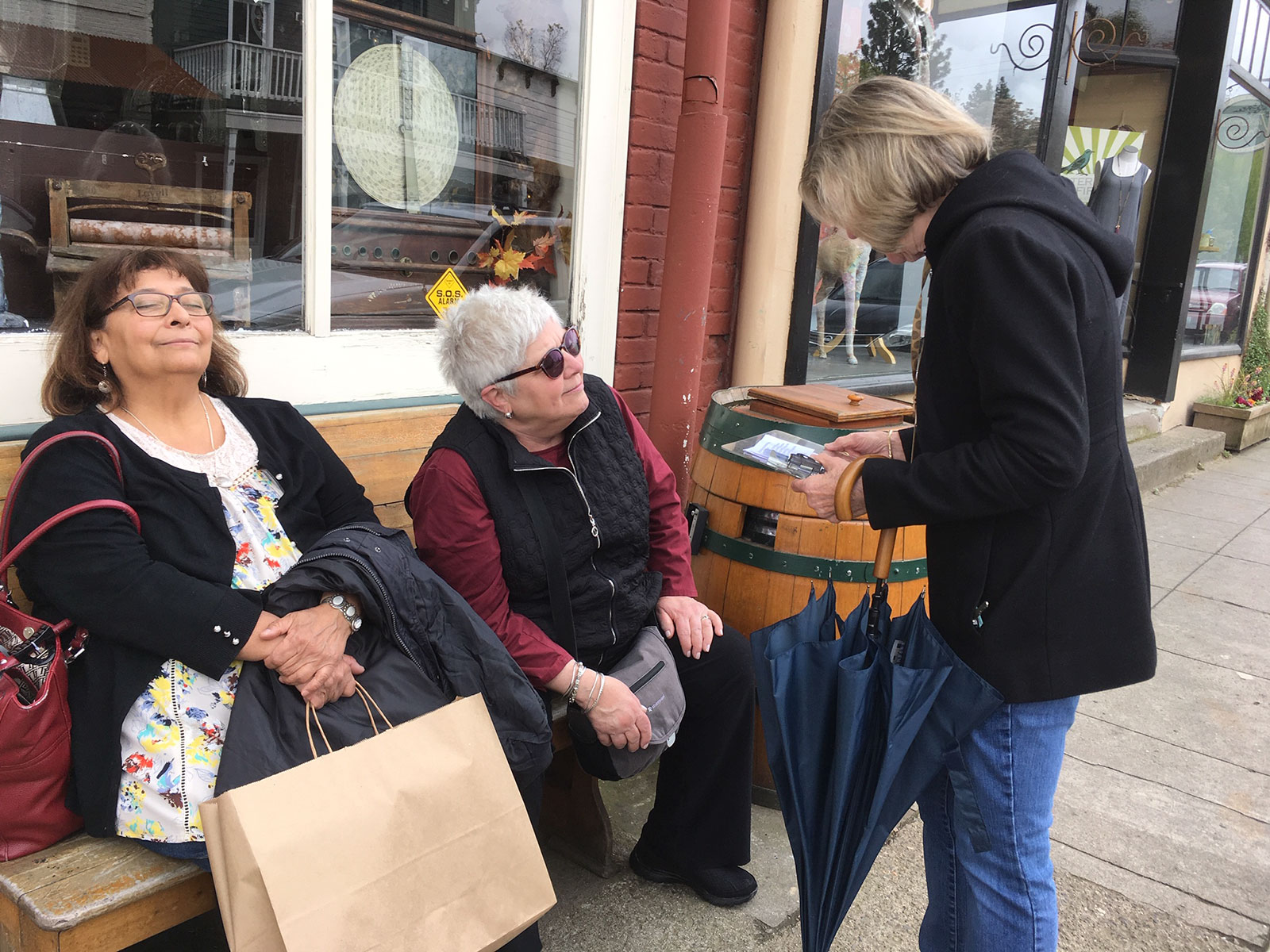 Poets on the Loose in Jacksonville! Anne Brooke reads a poemt to two ladies taking a break from shopping on California Street
