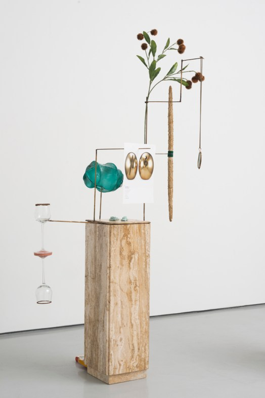"Laura Davis. ""Cups and Balls (Warm marble),"" travertine marble pedestal, brass, steel, plastic bag, vintage political button, plastic thistle, wooden candles, felt, paper, wine glasses, clay, rhinestones, books, string, agate, glue, microbeads, page from a Southeby's catalogue, 2014"