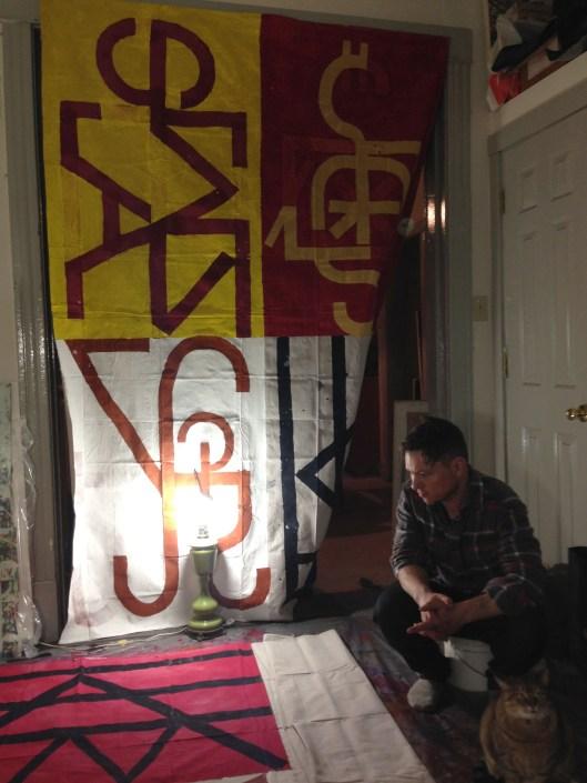 Elijah Burgher and his cat Monster in the artist's studio