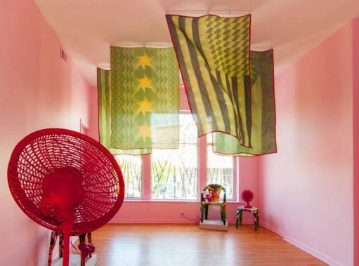 """Edra Soto. """"Say Everything,"""" 2014, installation view at The Lloyd Dobler Gallery mixed Media (flags, fans, plastic chairs, beach towels, tape, sand, cooler, pink light, latex paint). Photo by Michael Soto"""