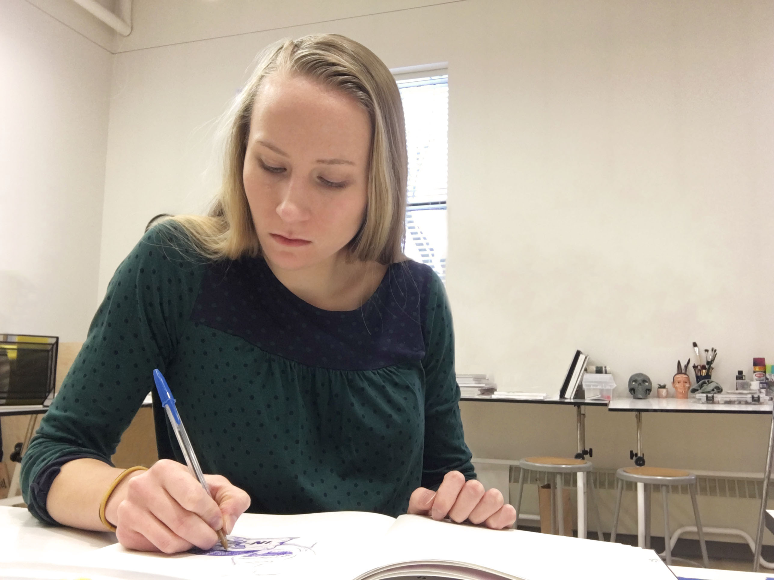Maddie LeBrun, featured artist, drawing in her sketchbook