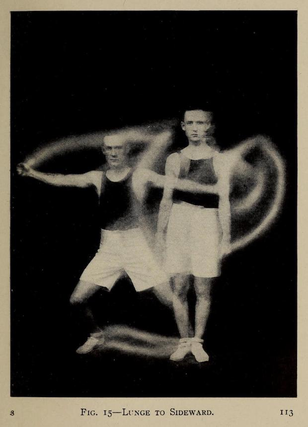 An old black and white photo showing a young white man standing and waving his arms around. The two versions of the man are superimposed over one another giving the photo an eerie quality