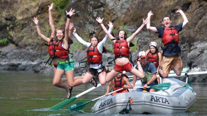 Kids jumping out of a raft into the Rogue River in Oregon with ARTA River Trips
