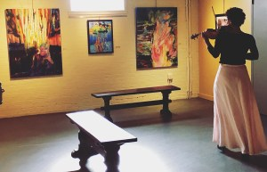 A woman wearing a long pink skirt plays the violin with her back to the camera in an art gallery with colorful paintings hanging on the wall.