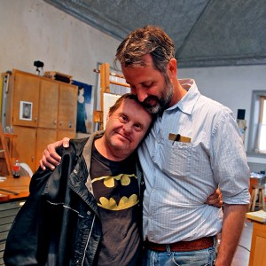 Two men, one of whom has down syndrome, are standing and hugging. They are in an art studio with easels and art in the background.